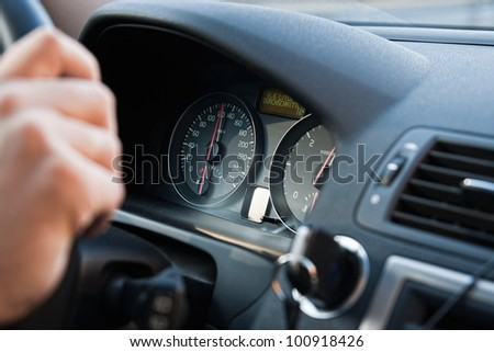 A man driving a car with his hand on the wheel