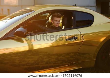A man driving an expensive car. A man is driving, a successful man is driving a car. Golden yellow car. A man at sunset driving. Success, expensive, freelance, businessman, famous.