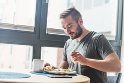 A man eating a healthy morning meal, breakfast at home. Fit lifestyle.