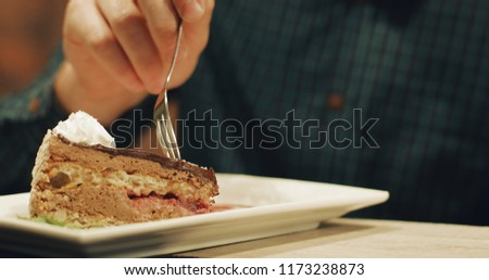 A man eats a delicious cake at the bar. The guy is having breakfast in the restaurant.