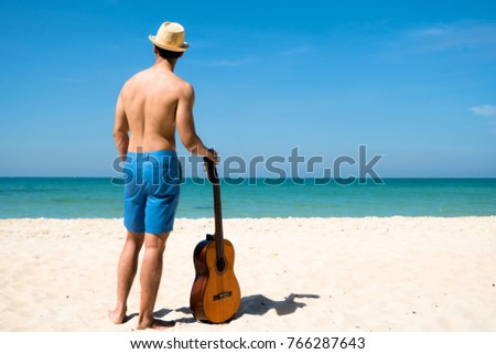 A man enjoy with the nature at the sea beach with guitar in hand, daylight sunny enjoyment #766287643