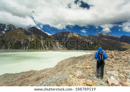 A man enjoys the view of the glacier and the lake from Glentanner Park Centre near Mount Cook, on a background of blue sky with clouds, snowy Southern Alps in New Zealand.