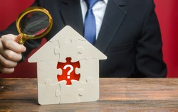 A man examines a house with a missing puzzle inside. Property valuation. Finding problems and structural hidden defects. Checking for compliance with the parameters criteria. Solving housing problems