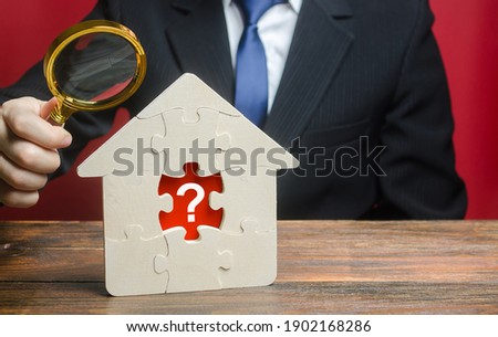 A man examines a house with a missing puzzle inside. Property valuation. Finding problems and structural hidden defects. Checking for compliance with the parameters criteria. Solving housing problems Stockfoto ©