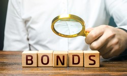 A man examines the inscription Bonds with a magnifying glass. Assessment of the value and profitability of securities. Investment. Terms and conditions. Face value. Raise money to finance new projects