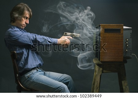 A man fires a gun in a retro TV.