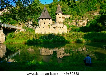 A man fishing on bank of Smotrych river near medieval ruins of Polish Gate in Kamianets-Podilsky. Calm quiet green place. Old towers reflecting in soothing water. Beauty of Ukrainian landscape.
