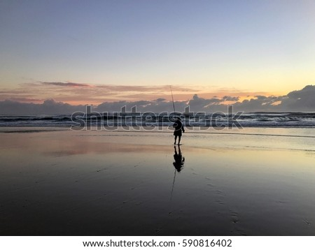 A man fishing on the beach at sunrise on the Gold Coast, Queensland, Australia #590816402