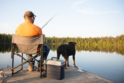 A man fishing outside at dusk on a lake in the summer on a wooden dock and a chair in Ontario Canada with his dog travel
