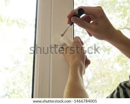 a man fixes a window, fastens a handle close up #1466784005