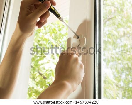 a man fixes a window, fastens a handle close up #1467394220