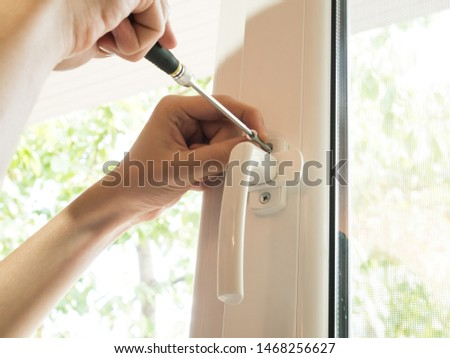 a man fixes a window, fastens a handle close up #1468256627
