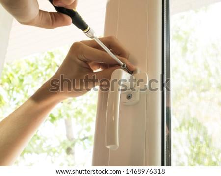 a man fixes a window, fastens a handle close up #1468976318