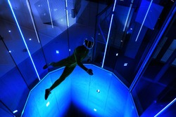 A man flier doing stunts in an indoor wind tunnel with neon lights