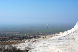 A man flies a paraglider over the white mountains, travertines in Pamukkale in Turkey. Turkey natural national landmarks