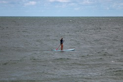 A man floats on the board in the Baltic Sea. Rest on the water. Paddle boarding