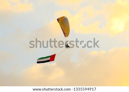 a man flying at the sunset holding uae flag, uae flag waving at the sunset, Flying paraglider with uae flag , uae flag day. united arab emirates