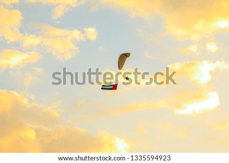 a man flying at the sunset holding uae flag, uae flag waving at the sunset, Flying paraglider with uae flag , uae  flag day