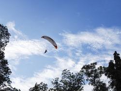 A man flying in the beautiful blue cloudy sky, parachute with a motor, paramotor. Sky driving. Extreme sport, adventure, freedom concept.