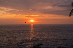 A man flying on a parasail against a orange sunset