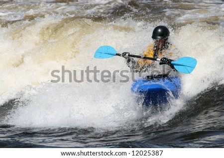 A man freestyle kayaking in the Champlain Rapids of the Ottawa River at Bates Island. Ottawa, Ontario. Canada.