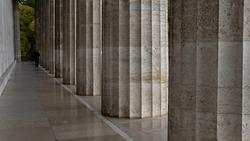 A man from behind walks along a stone portico made of marble  Ein Mann von hinten geht an einem steinernen Saeulengang entlang aus Marmor