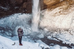 A man gazing at Kvernufoss waterfall in a close range where the ground is beautifully frozen on a sunny winter's day in South Iceland.