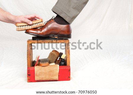 A man gets his shoes polished by a worker using a vintage shoe shine box with camel hair brushes, polishing rag, polish and a wooden shoe platform.