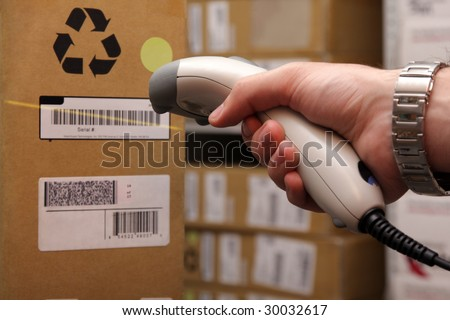 A man gets on the hip reader in operations directed on printed barcode. Warehouse scene.