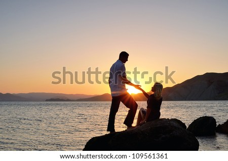 A man gives a woman's hand on the beach against the backdrop of the setting sun