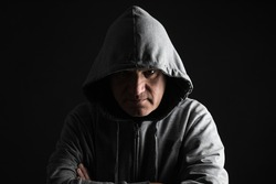 A man gives us a sinister look hiding in the darkness, with the face partly hidden with a gray hood. Fear and danger concepts. Studio shot with black background and copy space.
