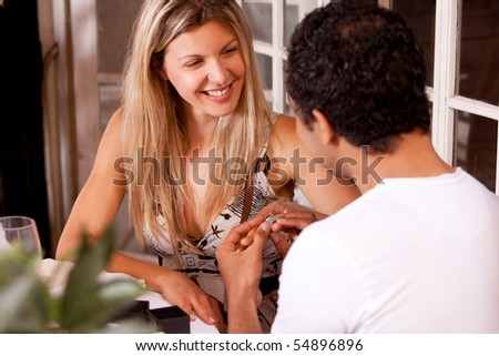 A man giving a ring as a gift to a female in an outdoor cafe