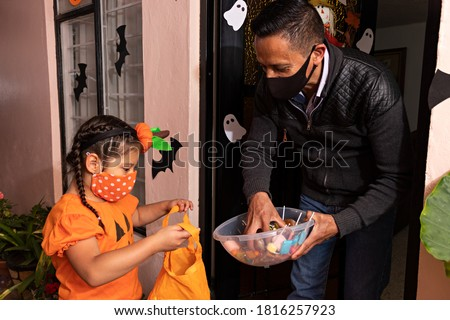 A man giving candies to a girl dressed in a pumpkin costume in the night of halloween Сток-фото ©