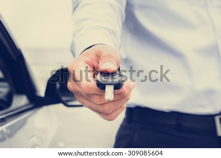 A man giving car key, vintage tone image