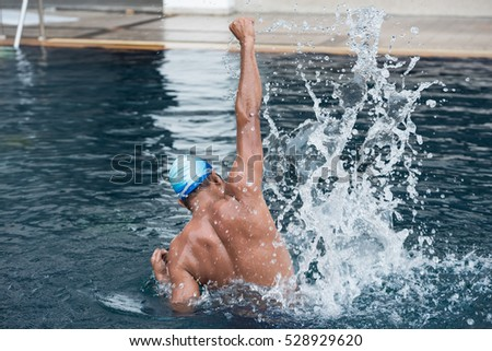 A man had jumping to adult swimming pool. He is a swimming athlete. He is a winner many match. His dream is swimmer win first prize of the world. He is fun when he jumping to the pool. #528929620