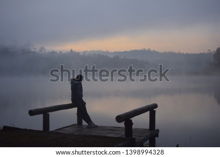 A man half standing and half sitting on a rail. He is in pontoon. It is twilight time. Fog are covered on the pond. Sierra is at backside of photo. He is along in picture.