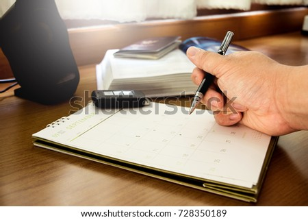 A man hand holding a pen for mark traveling day on the calendar, which lay on wooden counter desk  #728350189