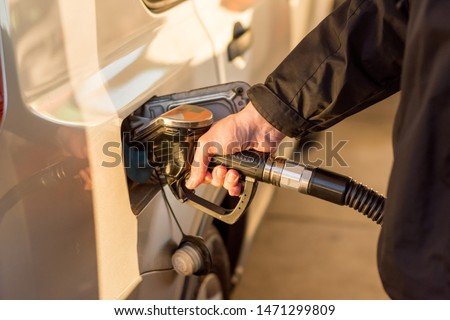 A man hand holding pump filling gasoline. Pumping petrol into the tank. A car refuel on gas station #1471299809