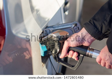 A man hand holding pump filling gasoline. Pumping petrol into the tank. A car refuel on gas station