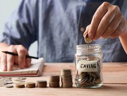 A man hand putting coins in a glass jar. Concept of retirement, save money and cash, finance, investing, growth management, business, financial planning.