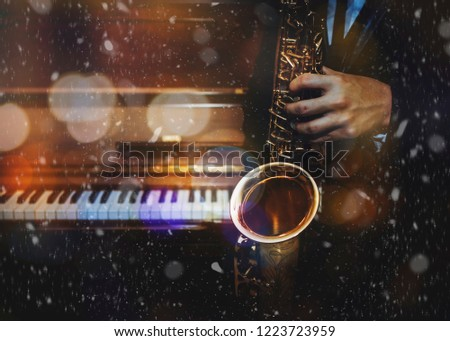 A man hands holding saxophone over piano keys with Bokeh light and snowfall in winter, Christmas night, Copy space