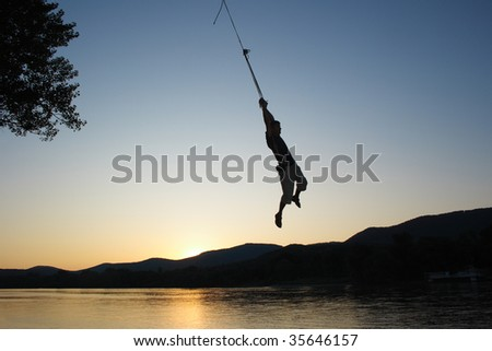 A Man hanging on a rope wing above a river at sunset. - stock photo
