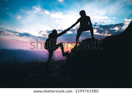 A man helping a woman to up on the mountain in hiking activity.teamwork concept.