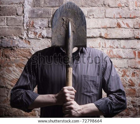 A man hides his face behind a shovel. Depersonalization, a metaphor.