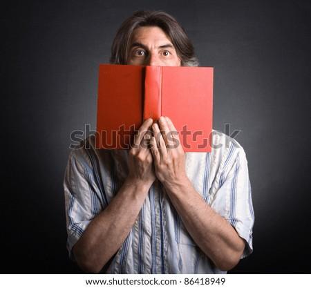 A man hiding behind an open book. - stock photo