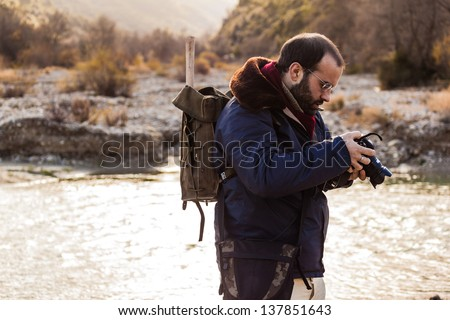 a man hiking and looking at the screen of a digital single lens reflex