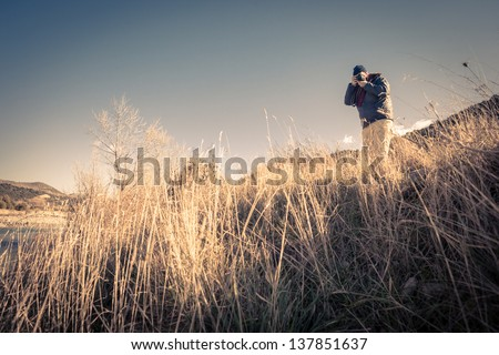 a man hiking and shooting with a digital single lens reflex