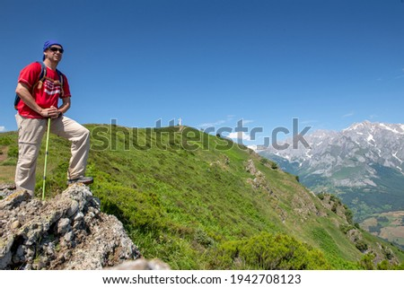 A man hiking in the Picos de Europa on the peak of Viorna near Potes, looking ahead, behind him are the high peaks and the stone cross on a cloudless summer day. Stockfoto ©