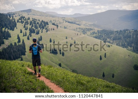 A man hiking on a trail with Vail's back bowls in the background during summer.