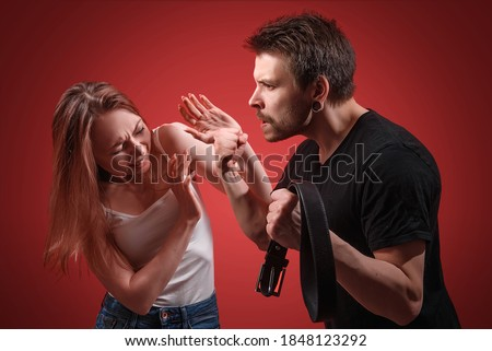 A man hits a defending woman with a belt during a scandal. Domestic violence against a girl. The husband mocks his wife. Quarrel in the family. Abusive relationships. Photo stock ©